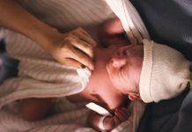 neonato accudito da una mano femminile