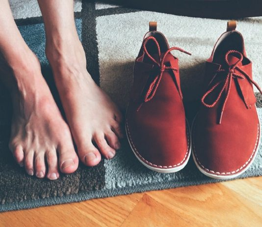 piedi nudi vicino a scarpe