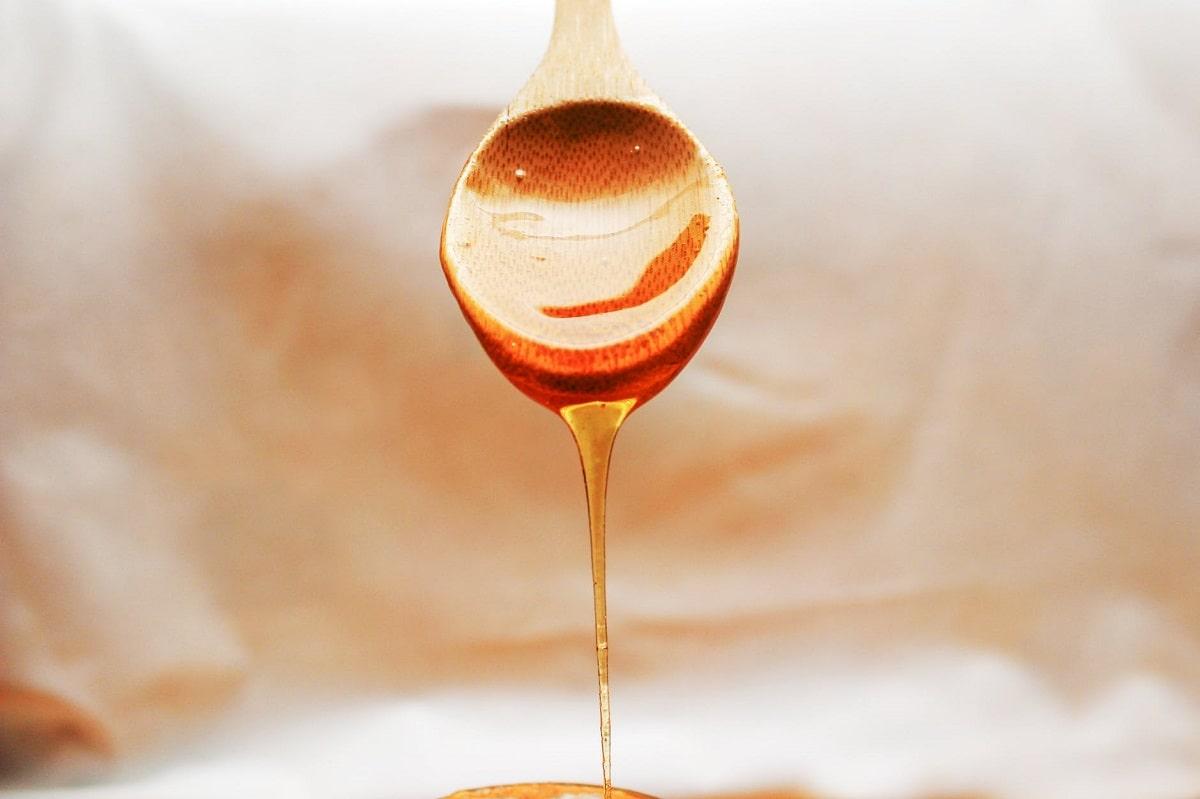 miele che cola da un cucchiaio di legno