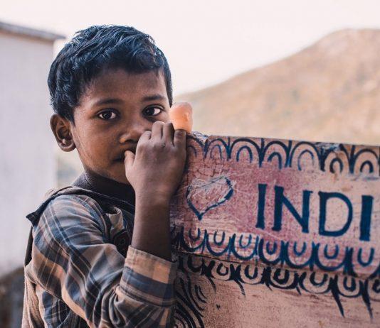 bambino appoggiato ad un cartello