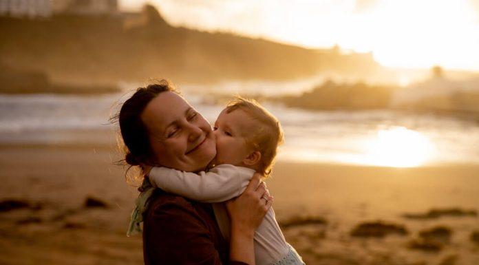madre-che-bacia-bambino-sulla-guancia