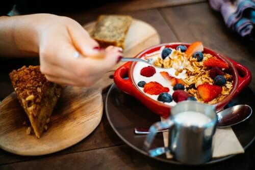 persona-con-cucchiaio-e-ciotola-in-ceramica-rossa-rotonda-con-cereali-fa-una-sana-colazione