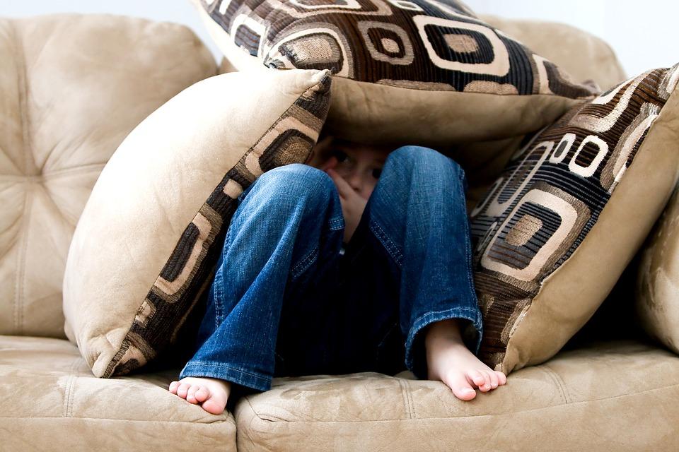 Bambino che si nasconde sotto ai cuscini