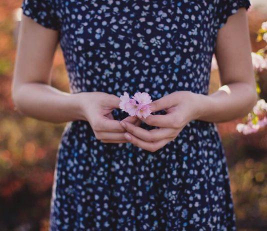 donna-in-abito-floreale-blu-e-bianco-con-fiore-rosa-a-portata-di-mano