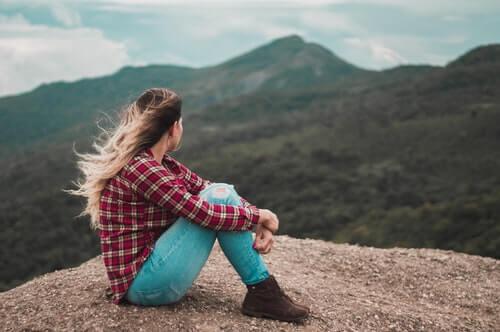foto-di-vista-laterale-della-donna-che-si-siede-sulla-terra-che-sormonta-una-collina