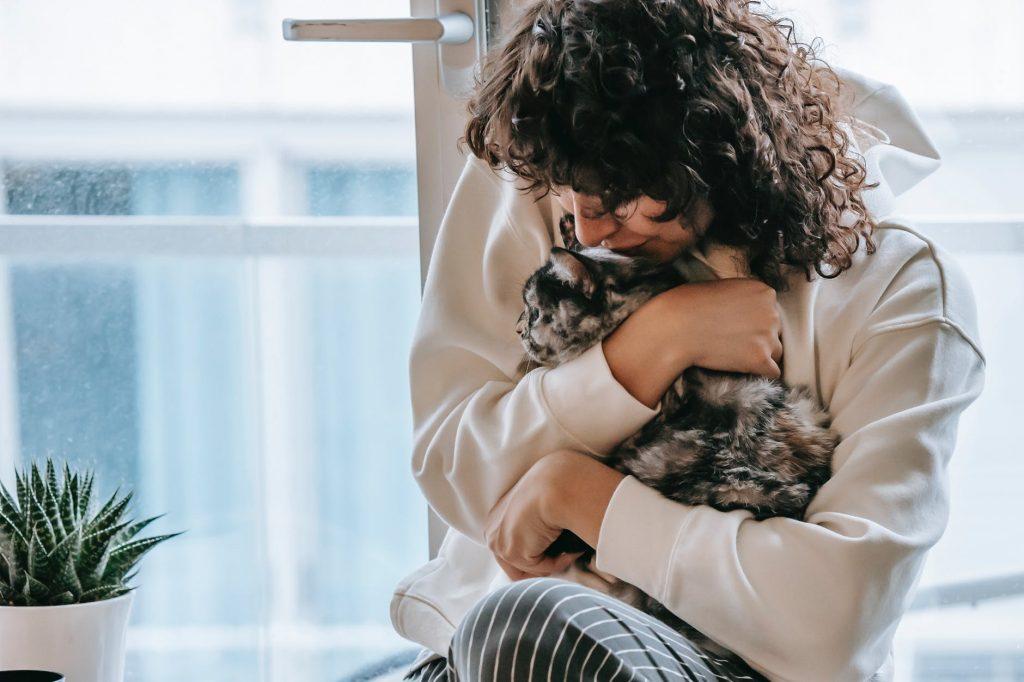 Donna che abbraccia un gatto