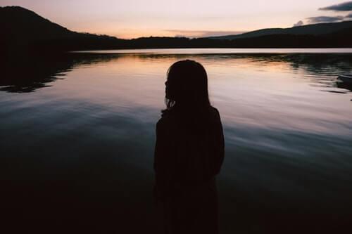silhouette-di-donna-in-piedi-vicino-al-corso-di-acqua-in-solitudine