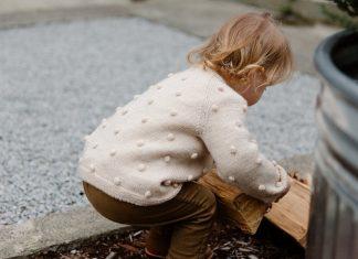 Bambino che cerca di alzare un pezzo di legno