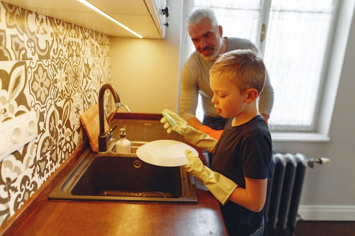 bambino che aiuta nelle faccende domestiche lavando i piatti