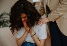 Ragazza che piange e due braccia che la consolano