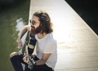 uomo-coi-capelli-lunghi-suona-la-chitarra-sulla-riva