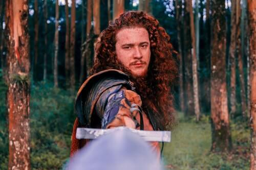 guerriero-coi-capelli-lunghi-rossi-boccoli-impugna-una-spada-nella-foresta