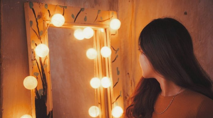 donna che si sta per specchiare