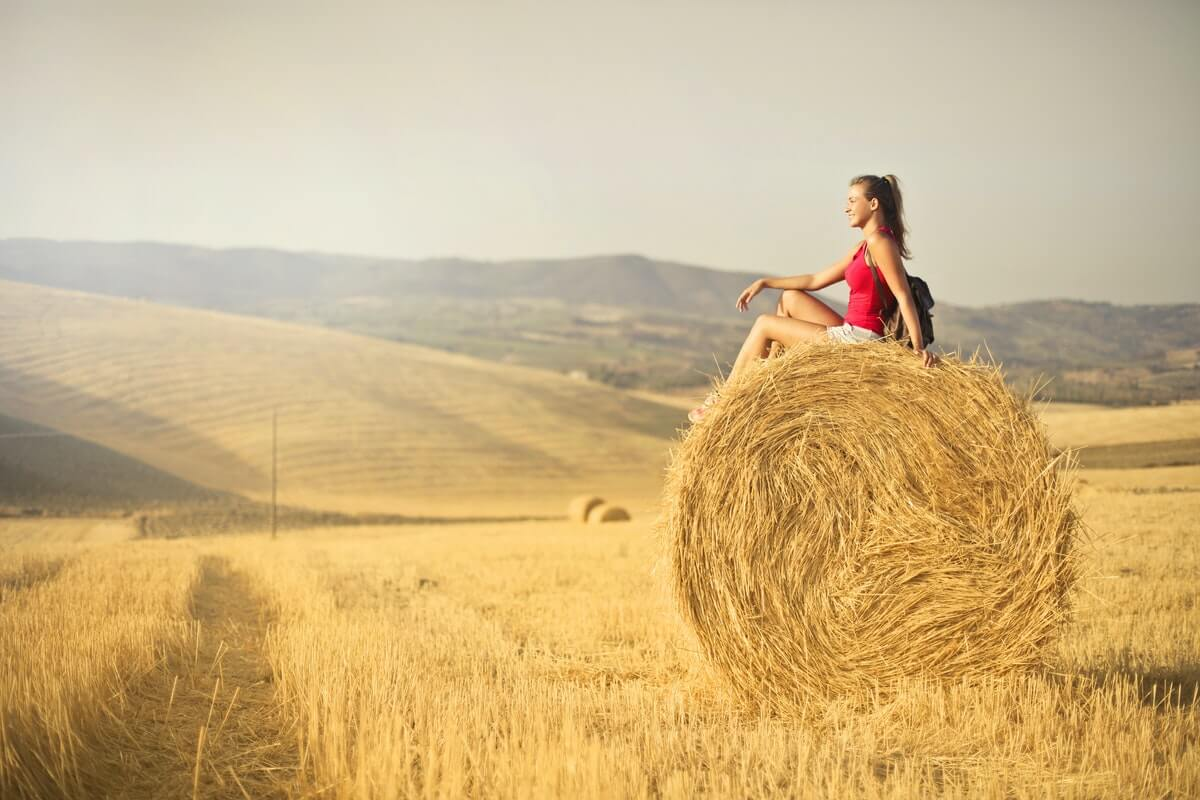 donna-seduta-sul-fieno-in-mezzo-a-un-campo