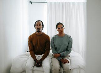 coppia seduta sul letto con sguardo triste