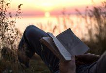 uomo che legge un libro in riva ad un lago
