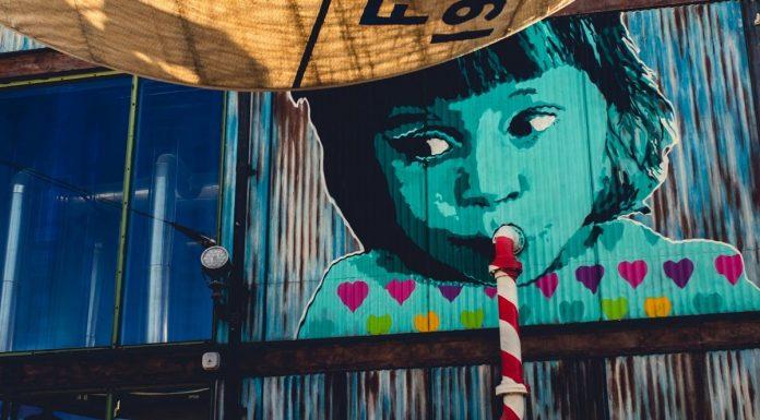 murales di un bambino che sorseggia tramite una cannuccia che in realtà è un tubo