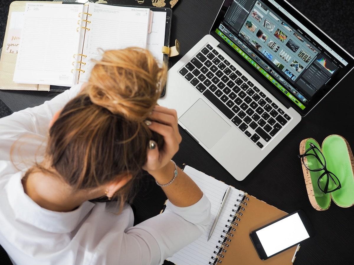 donna china sulla scrivania con computer e telefono