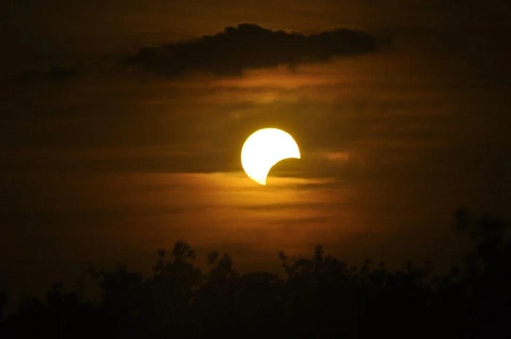sole nel cielo oscurato parzialmente dalla luna