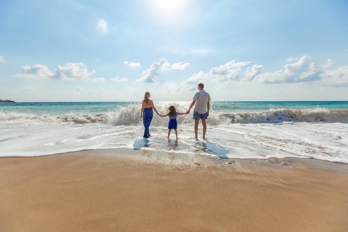 madre-e-padre-tengono-il-bambino-per-mano-davanti-alle-onde-del-mare
