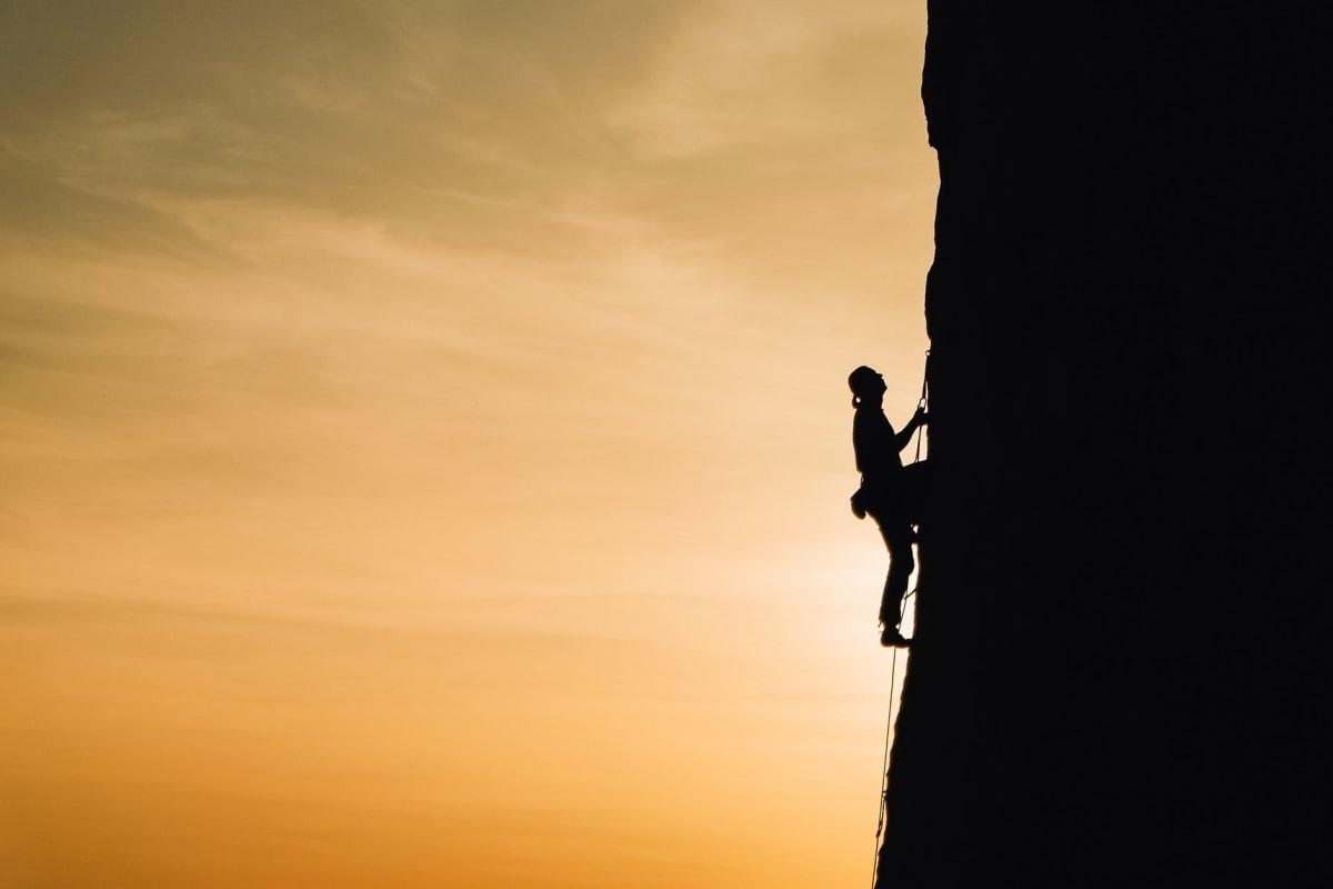 uomo che si arrampica sulla roccia