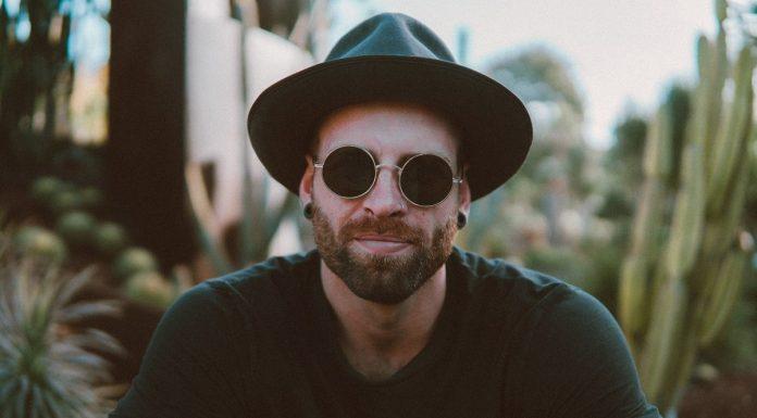 uomo con occhiali e tatuaggi