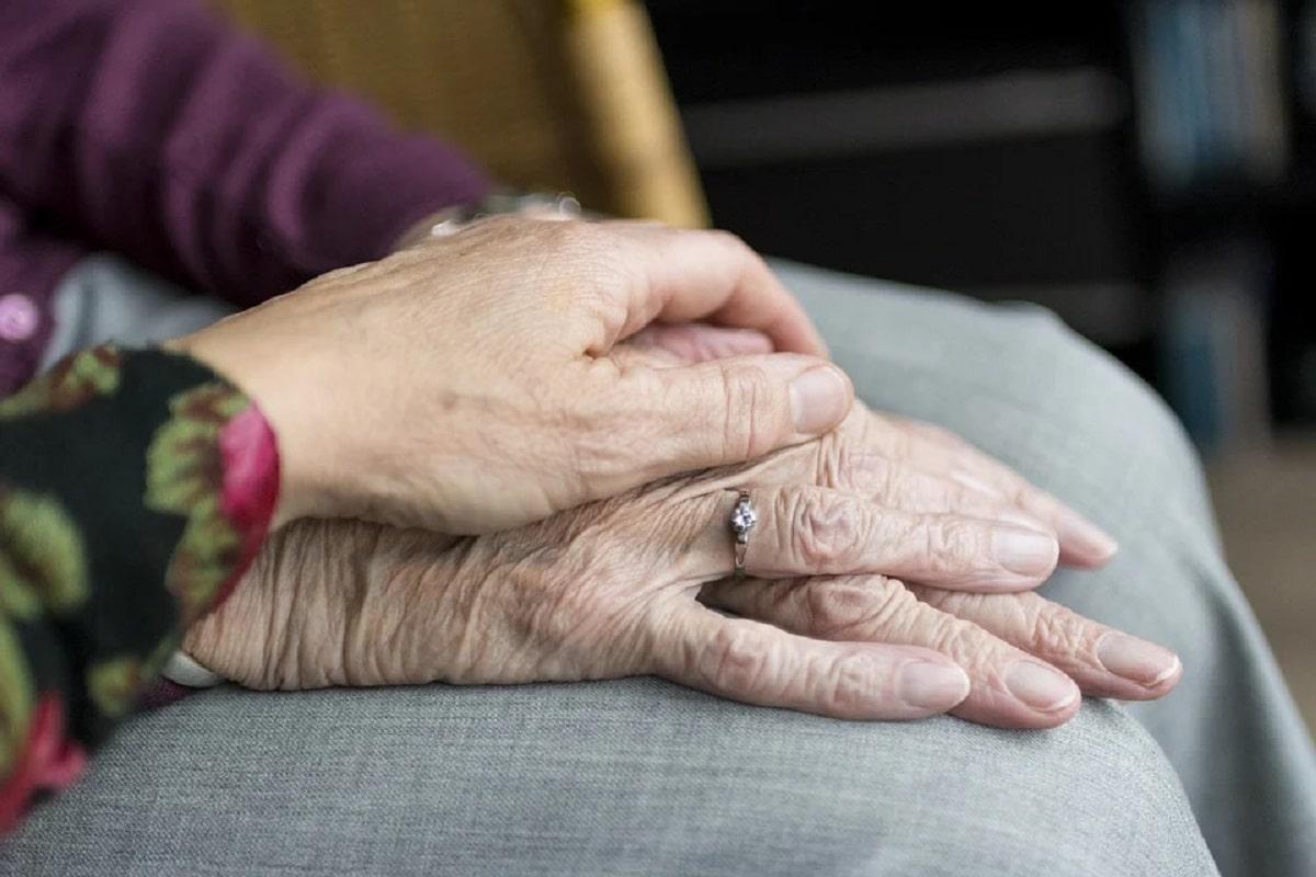 mano che accarezza mano anziana