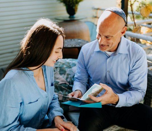 padre che mostra un biglietto alla figlia