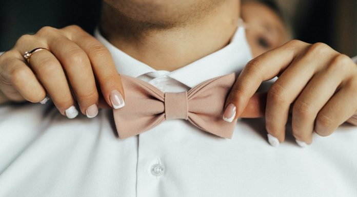 mani di donna che sistemano il farfallino di un uomo in camicia