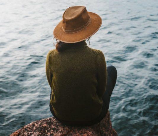 donna seduta in riva al lago